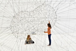 Young people in a futuristic construction made of cords