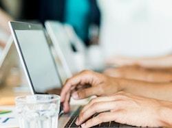 Men typing on computer